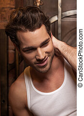 Portrait of sexy man in white T-shirt. Smiling and looking away