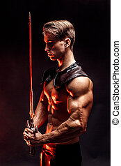 Portrait of sexy muscular concentrated man holding sword. -...