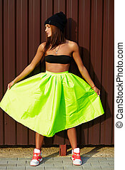 portrait of sexy teenager urban modern young stylish woman girl  model in bright modern cloth in green colotful skirt outdoors in the street standing near wall