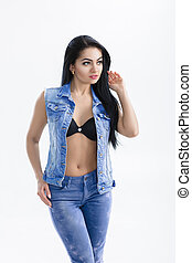 portrait of sexy young brunette woman with long hair in denim vest on white background.