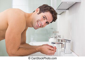 Portrait of shirtless man washing face in bathroom - Side ...