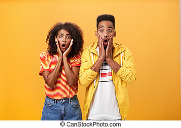 Portrait of shocked and stunned speechless girlfriend dropping jaw from amazement with boyfriend feeling amazed from shook news posing together surprised and astonished over orange wall. Lifestyle.
