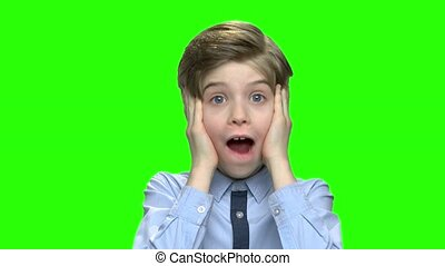 Portrait of shocked boy touching his cheeks.