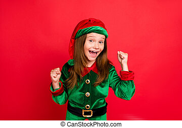 Portrait of shocked elf kid in green hat cap with long red head hairstyle, raising her fists celbrate newyear party wearing fairy costume isolated over red background