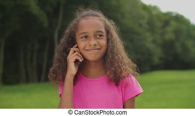 Outdoor portrait of shy adorable elementary age african american girl twisting her curly hair on finger, thinking about escapade, looking with innocent modest smile while standing in summer nature.