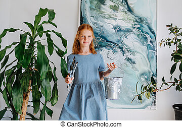 Portrait of shy teenage redhead girl with bunch of brushes in hand.