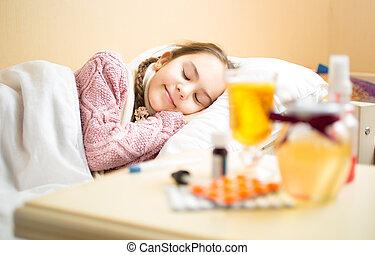 Portrait of sick girl in woolen sweater lying in bed