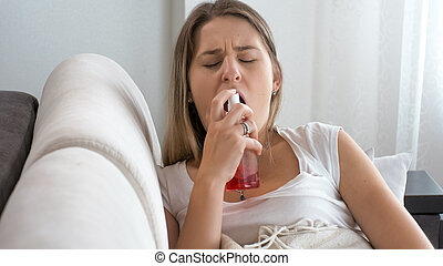 Portrait of sick young woman sitting on sofa and using throat spray