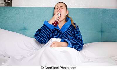 Portrait of sick young woman using throat spray to reduce pain