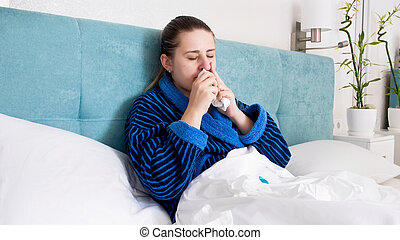 Portrait of sick young woman with flu lying in bed and using nasal spray