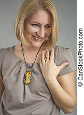 portrait of sincere smiling blond woman with lifted hand