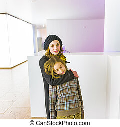sisters hugging and take care in a white room