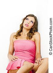 portrait of sitting woman wearing pink dress