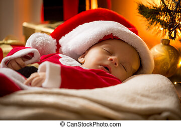 portrait of sleeping baby boy in Santa cap at living room