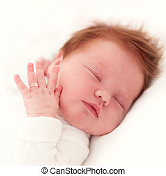 portrait of sleeping newborn baby girl with finger ring