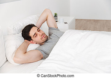 Portrait of sleepy unshaved man in casual t-shirt, having nap alone at home in bed with white clean linen putting hands under head