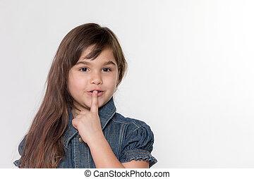 Portrait of slightly smiling little girl gesturing shush