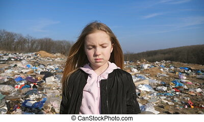 Portrait of small female child looks into camera against the blurred background of dirty garbage dump. Little serious girl stands in junkyard at countryside. Concept of environmental pollution problem.