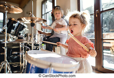 Portrait of small girl indoors at home, playing drums.