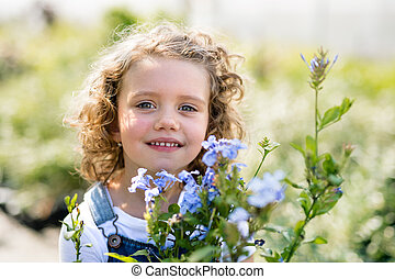 Portrait of small girl standing in the backyard garden.