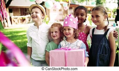 Portrait of small girl with friends and presents outdoors in...