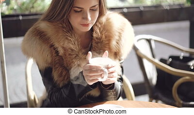 Portrait of smart girl drinking a cup of hot coffee in cafe. 4K