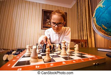 Portrait of smart girl make move on chess board