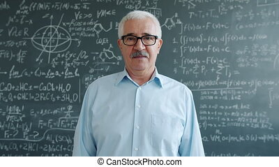 Portrait of smart mature man standing in class with serious face looking at camera