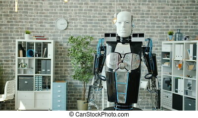 Portrait of smart robot rolling in office room looking at camera moving hand