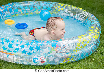 Portrait of smiling 1 year olf baby boy swimming in inflatable swimming pool at house backyard