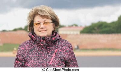 Portrait of smiling adult woman aged 60s outdoors - Portrait...