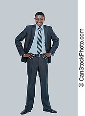 Portrait of smiling African American business man standing over white background.