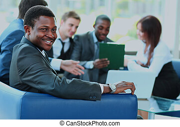 Portrait of smiling African American business man with executives working in background.