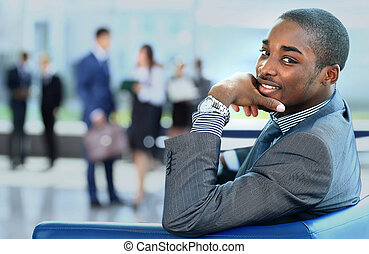 Portrait of smiling African American business man with executives working in background