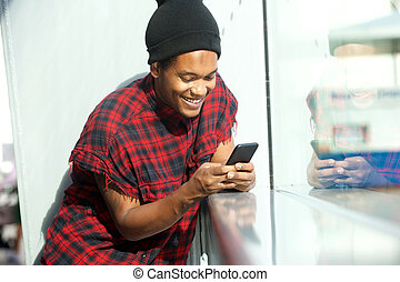 smiling african american man looking at mobile phone