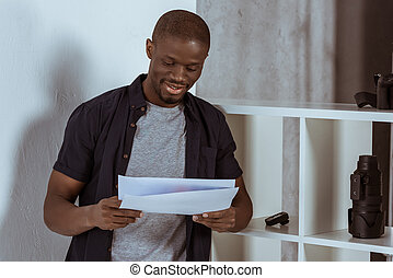 portrait of smiling african american man with papers in hands
