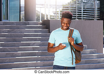 smiling african american student looking at cellphone