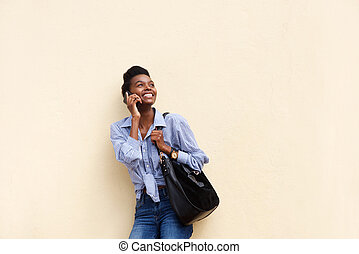 smiling african american woman against wall with cellphone