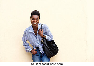 smiling african american woman against wall with handbag