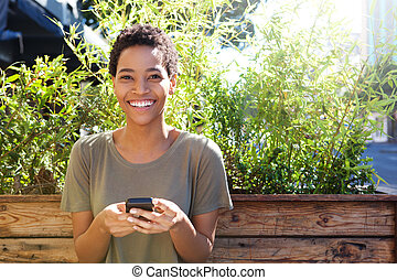 smiling african american woman holding mobile phone outdoors