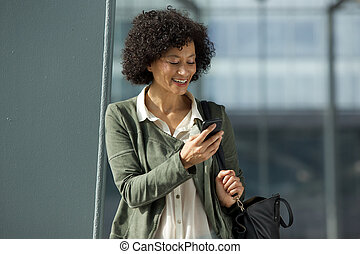 smiling african american woman looking at cellphone