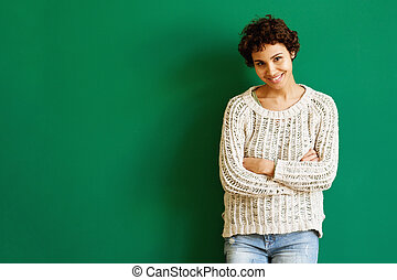 smiling african american woman standing against green wall with arms crossed