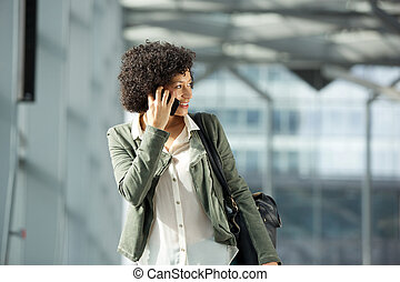 smiling african american woman talking with cellphone