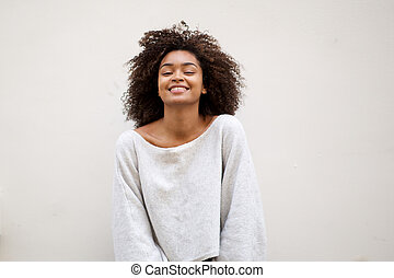 smiling african american woman with curly hair against white wall