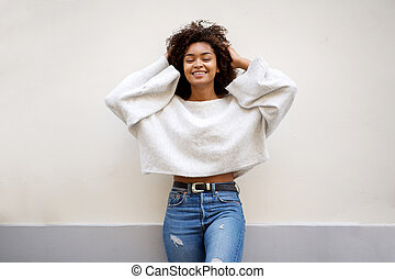 smiling african american woman with hands in hair against white wall