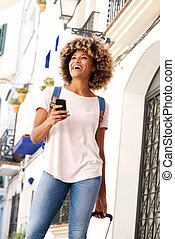 smiling african female standing with bag and mobile phone outdoors