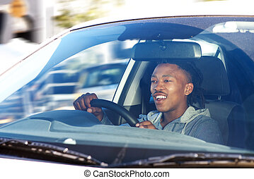 smiling african man driving car in city