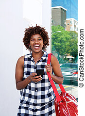 smiling african woman in the city with cellphone and bag