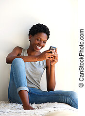 smiling african woman relaxing at home and looking at smart phone