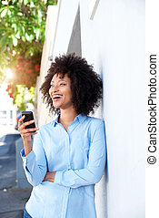 smiling african woman standing by a wall outside holding cellphone